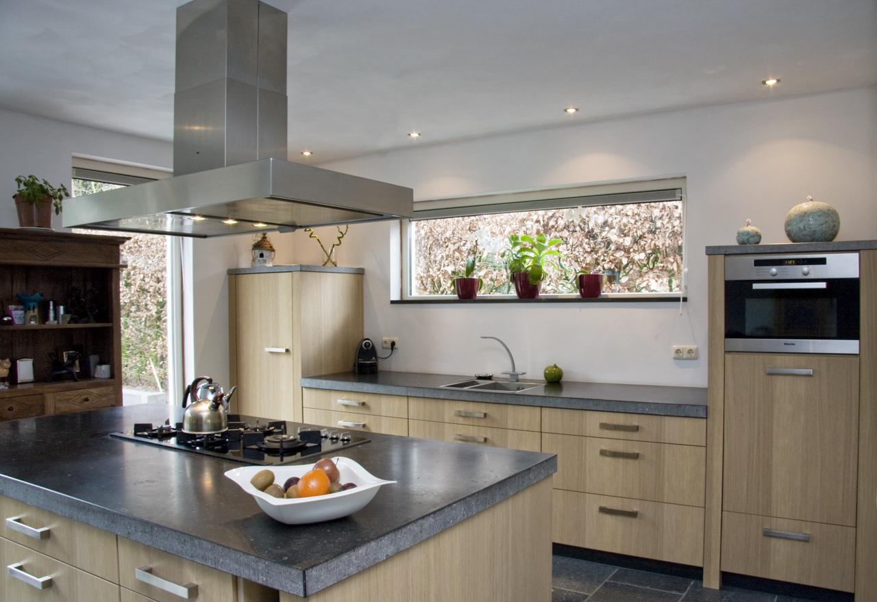 De beton look en hout look fronten geven deze keuken een